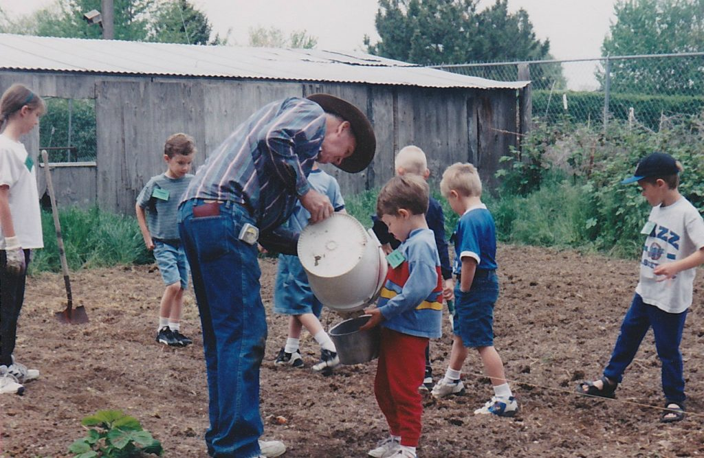 a group of kids helping a man plant his garden