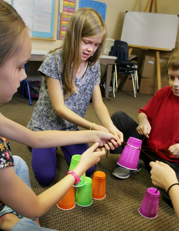 kids learning teamwork with a plastic cup challenge