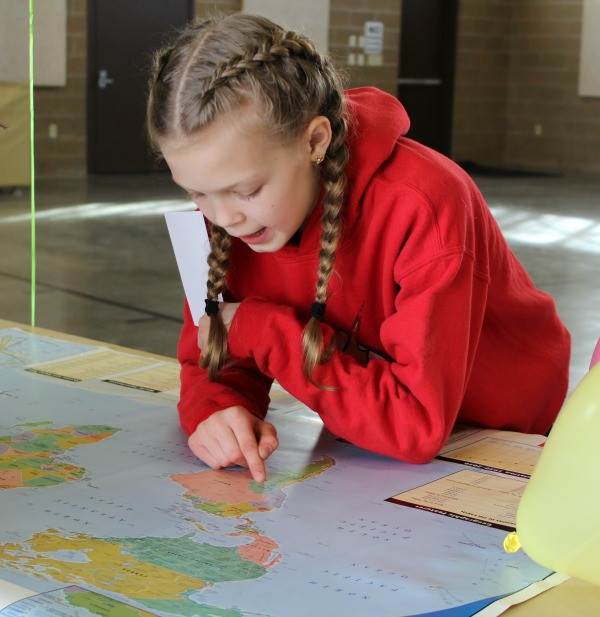 girl finding a location on a map