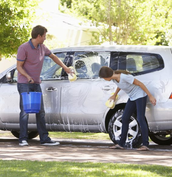 Dad spending time with daughter while washing the car