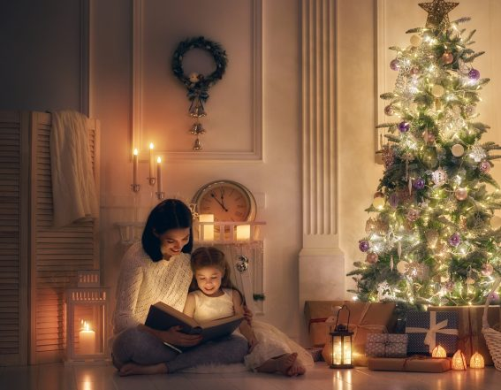 Pretty young mom reading a book to her cute daughter near Christmas tree indoors.
