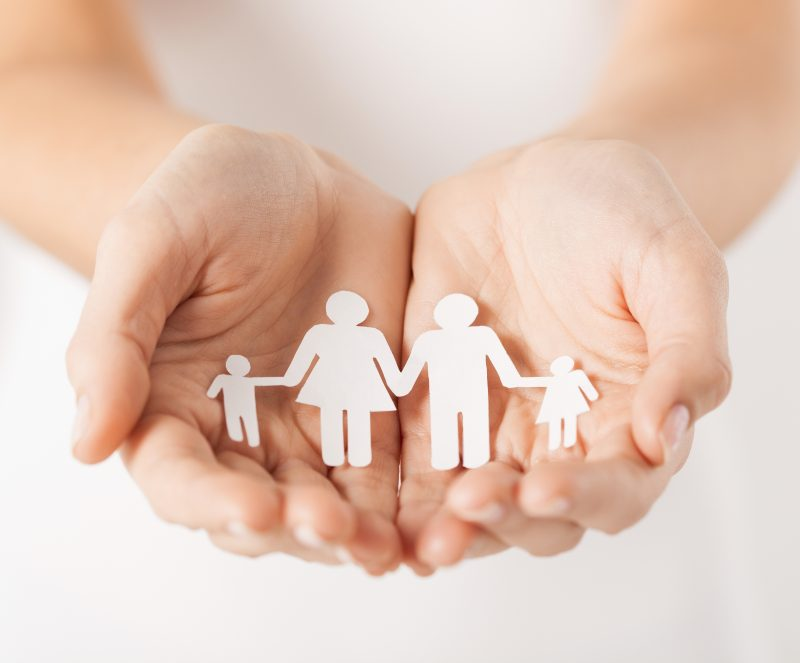 close up of woman's cupped hands showing paper man family