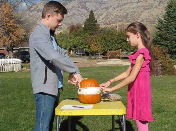 boy and girl putting rubber bands around a pumpkin