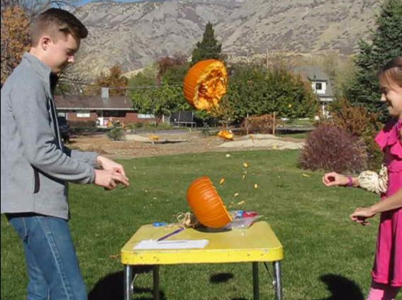 boy and girl busting a pumpkin in half using rubber bands