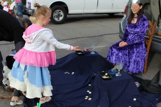 kids having fun doing a coin toss at a Halloween healthy trunk or treat