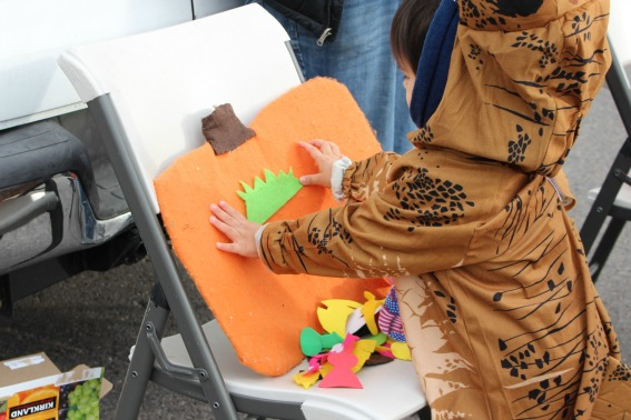 kids making fun Halloween felt faces at a trunk or treat