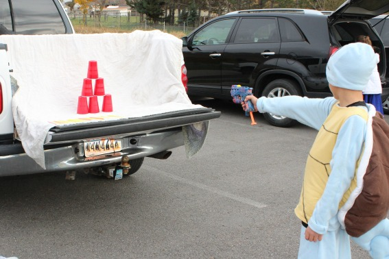 kids knocking down stacked cups at a Halloween healthy trunk or treat