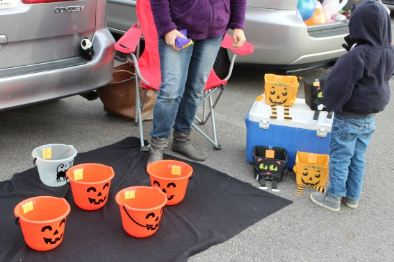 kids tossing bean bags into buckets at a Halloween healthy trunk or treat