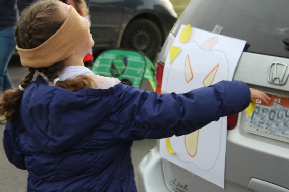 kids playing pin the nose on the jack-o-lantern at a Halloween healthy trunk or treat
