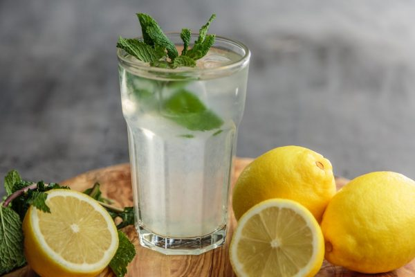 A glass of lemonade with mint leaves in it, surrounded by whole and cut lemons